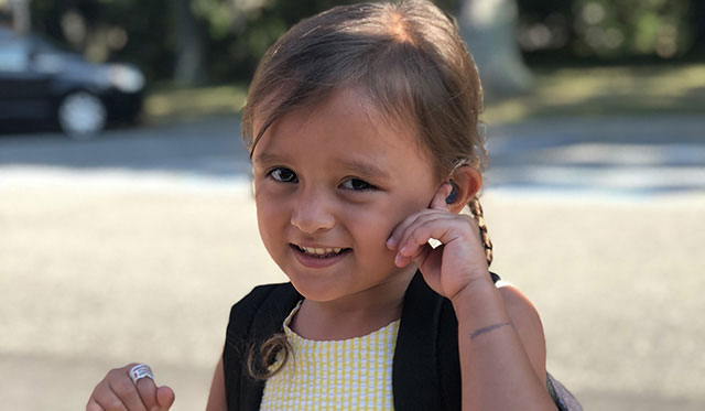 Female Mill Neck Manor student pointing to her hearing aid